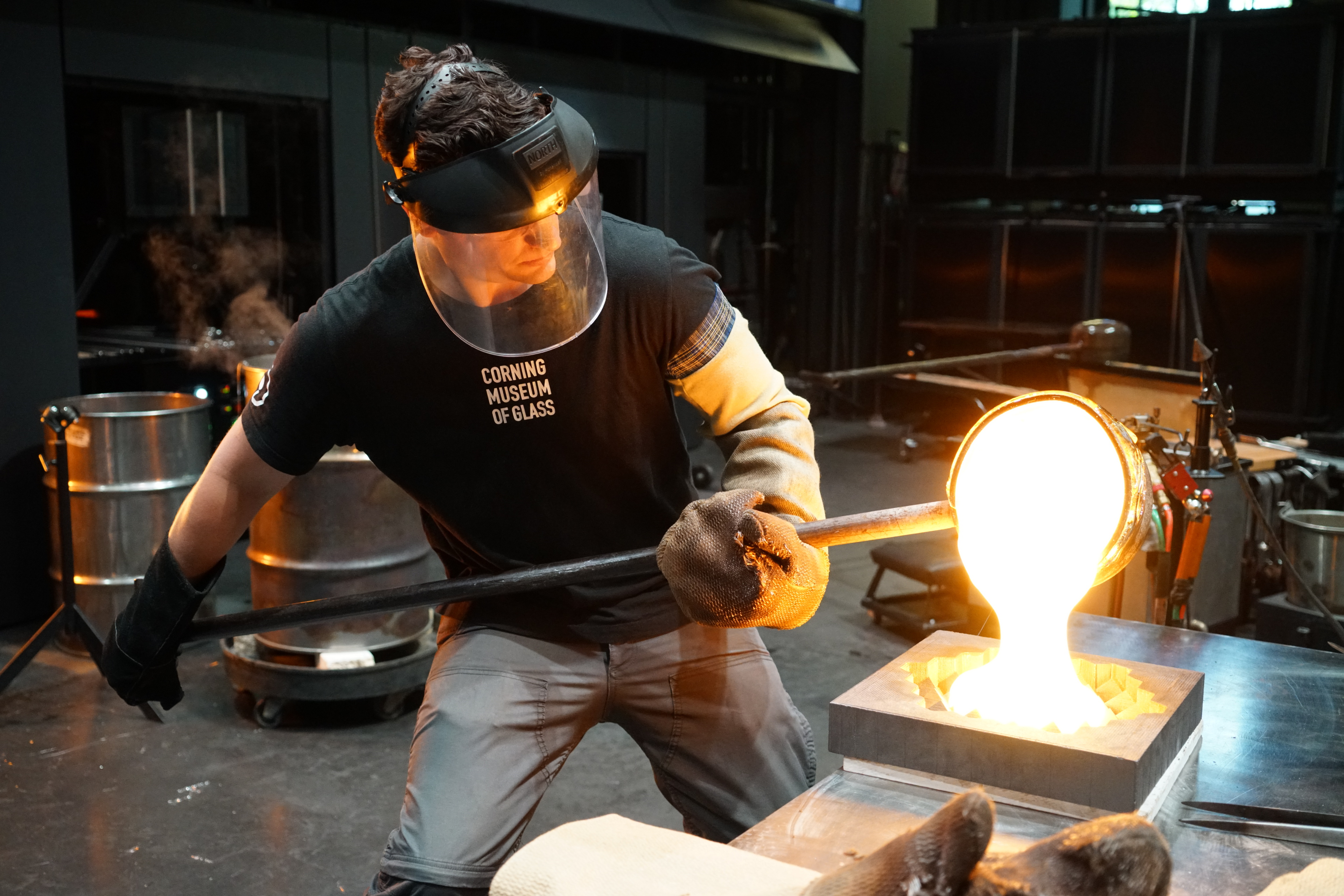 A glassworker pours molten glass into a mold while wearing protective gloves and mask.