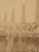 old sepia photo of outside of glassworks, with workers