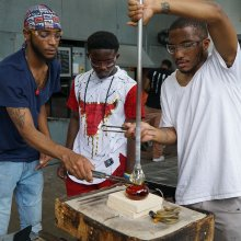 Two young men assist another with a glassblowing project