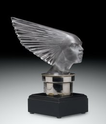Automobile Mascot, Victoire (Victory), designed 1928. Mold-pressed glass, acid-etched; metal radiator cap, wood base. H. 23 cm, W. 24.6 cm, D. 10.1 cm. (2011.3.345, gift of Elaine and Stanford Steppa)