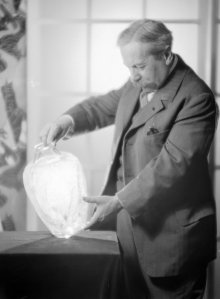 Photograph of René Lalique looking at a colorless version of the Lézards et bleuets (Lizards and bluets) vase, designed in 1913. The photo was taken around 1925. The Corning Museum of Glass has an opaque black version of this vase.