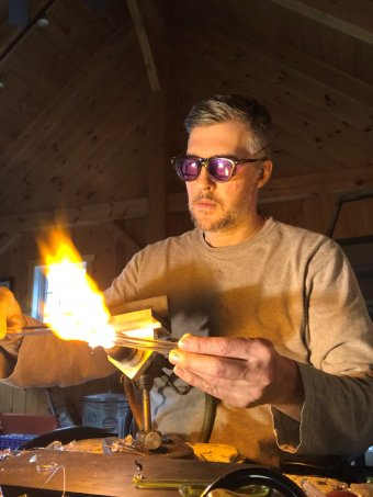 man wearing purple safety glasses heats a tube of clear glass on a torch in a wood paneled room with a high vaulted ceiling